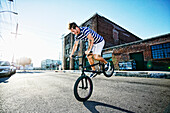 Caucasian man riding BMX bike on street