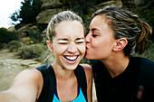 Woman kissing cheek of friend outdoors