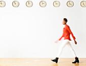 Mixed race businesswoman walking under clocks