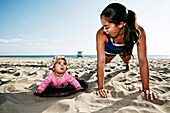 Mother and daughter doing push-ups at beach