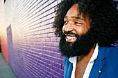 Mixed race man smiling outdoors near purple wall