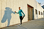Mixed race athlete stretching on sidewalk
