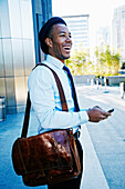 Black businessman using cell phone outside office building