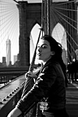 Young Adult Woman on Brooklyn Bridge Looking into Distance, New York City, New York, USA