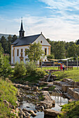 Water activities on creek along Bischofsheimer Was(s)ErlebnisWeg with Katholische Friedhofskapelle St. Joseph chapel behind