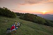 Participants of pilgrimage from Würzburg enjoy a picnic near summit cross on Kreuzberg mountain at sunset