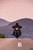 Man rides Harley-Davidson motorcycle on road to Point Alpha Memorial with Gehilfersberg mountain behind