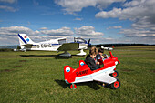 Young boys in toy airplanes at Kinderflugplatz adjacent to Flugplatz Wasserkuppe air field