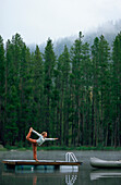 Woman doing yoga on a dock in the middle of a lake. Montana