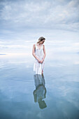 A young woman stands in a lake with a vast sky.