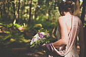 A young woman holds a bouquet of flowers in a forest setting.