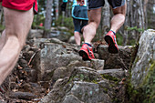 Trail runners on hard granite rocks adn ledges in the White Mountains of NH.