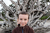 Boy in front of large piece of driftwood, portrait