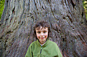 Boy in front of tree trunk, portrait
