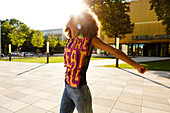 Junge, afroamerikanischen Frau genießt die Sonne am Lenbachplatz, München, Bayern, Deutschland