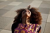 Young afro-american woman sitting relaxed and laughing on a graphical floor, Lenbachplatz, Munich, Bavaria, Germany