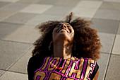 Sportliche junge afroamerikanische Frau entspannt lachend auf grafischem Boden, Lenbachplatz, München, Bayern, Deutschland