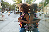 Young afro-american woman leaning relaxed onto a glass building in urban scenery, Munich, Bavaria, Germany