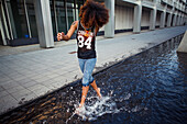 Sportive, young afro-american woman running through a water fountain in urban scenery, Munich, Bavaria, Germany