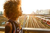 Junge afroamerikanische Frau im Gegenlicht mit Bahnhof und Gleisen, Hackerbrücke, München, Bayern, Deutschland