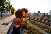 Junge afroamerikanische Frau trinkend im Gegenlicht  in urbaner Szenerie mit Gleisen, Hackerbrücke, München, Bayern, Deutschland