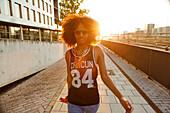 Coole, sportliche junge afroamerikanische Frau geht im Gegenlicht in moderner urbaner Szenerie, München, Bayern, Deutschland