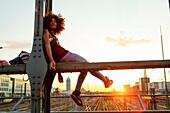Junge afroamerikanische Frau sitzt im Abendlicht auf Stahlträger in urbaner Szenerie mit Gleisen, Hackerbrücke, München, Bayern, Deutschland