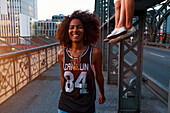 Young afro-american woman walking and laughing on a old steel bridge in urban scenery, Hackerbruecke bridge, Munich, Bavaria, Germany