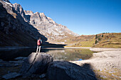 A hiker on the shore of the mountain lake Oberblegisee, Glarus Alps, canton of Glarus, Switzerland