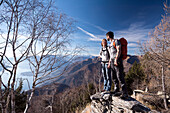 A couple standing on an old stone wall near the summit of Sassariente near Bellinzona and Locarno, Lepontine Alps, canton of Ticino, Switzerland