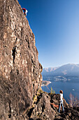 A couple is climbing on the crags of Baladrum above Ascona, in the background Lake Maggiore, canton of Ticino, Switzerland