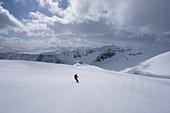 Eine Skitourerin in der Abfahrt vom Saudaneshnjúkar in der Nähe von Dalvík, Tröllaskagi respektive Troll-Halbinsel, Island