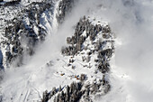 An artificially triggered massive avalanche is racing down the full-scale avalanche dynamics test site of the Swiss WSL Institute for Snow and Avalanche Research (SLF) near some uninhabited houses, Vallée de la Sionne, Western Bernese Alps, canton of Vala