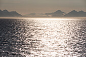 Midnight sun on the waters of Isfjorden, near Longyearbyen, behind it the summits and glaciers of the northwestern shore of the fjord, Spitsbergen, Svalbard, Norway