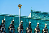 A flagpole with a golden ship on the top, in front of the in the historical style of neorenaissance built Hamburg city hall, Hamburg, Germany
