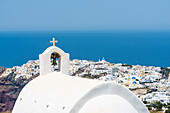 The bell tower of a Greek orthodox chapel with view to the village Oia and the Mediterranean Sea up to the horizon, Oia, Santorin, Cyclades, Greece