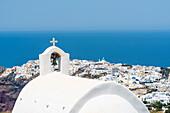 Der Glockenturm einer Griechisch Orthodoxen Kapelle mit Blick auf den Ort Oia und das Mittelmeer bis zum Horizont, Oia Santorin, Kykladen, Griechenland