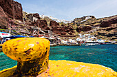Harbour of Amoudi Bay with view at the steep coast and the village with the windmill and the traditionally built houses, Oia, Cyclades, Santorini, Greece