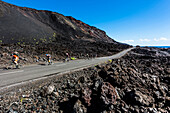 Cyclist on a street at the south point in the volcano area, El Charco, La Palma, Canary islands, Spain