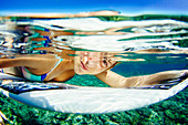 Underwater portrait of professional surfer Lucia Marti??o with her surfboard