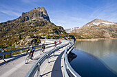 Four road bikers on the dam of the Emosson reservoir lake in the Alps on the border of France and Switzerland. It is an early morning training session of the local cyclists. The climb from Martigny to Finhaut will be stage 17 of the 2016 Tour de France on