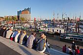 Menschen sitzen auf den Terrassen am Hafen, Blick zur Elbphilharmonie, Hamburg, Deutschland