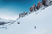Snowshoe hiker beneath the Villnoesser Geisler, Gruppo delle Odle, Dolomites, Unesco world heritage, Italy