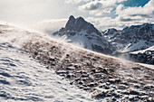 Snow blowing on top of the Gabler mountain,the Peitlerkofel in the background, Dolomites, Unesco world heritage, Italy