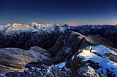 Hiker standing on top of Duerrenstein after sunset, panoramic view in direction to the Tre Cime di Lavaredo, Sexten Dolomites, Unesco world heritage, Italy