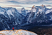 Hiker enjoying panoramic mountain view on an early morning, Bellunesi Dolomites, Unesco world heritage, Italy
