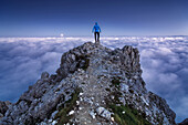 Hiker standing on a rock over a sea of fog in the early morning, Rosengarten mountain range, Dolomites, Unesco world heritage, Italy