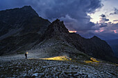 Hiker passes over the Gliederscharte mountain gorge at nightfall, Pfitsch, Part of the long distance hiking trail from Munich to Venice, South Tyrol, Italy