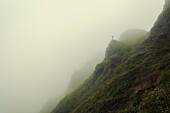 Hiker standing on a rock, surrounded by fog in the Pfunderer Mountains, South Tyrol, Italy