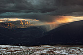 View from Koenigsangerspitze at sunset in the direction of Eisack Valley, On the left the Dolomites, Unesco world heritage, reflecting the last light of the day,  A group of motocross bikers watching the storm front pass through, South Tyrol, Italy